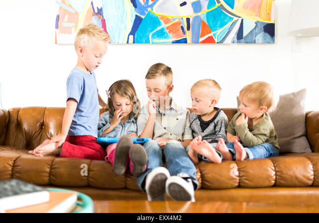 Children (2-3, 4-5, 6-7) sitting on sofa and using digital tablet - Stock Image