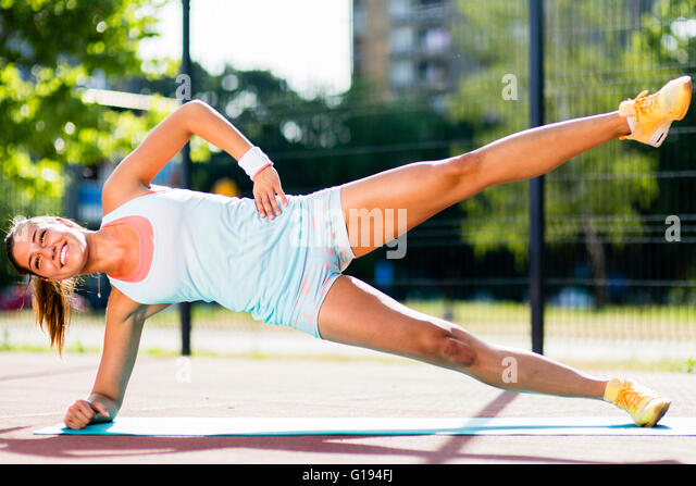 Beautiful woman doing exercises outdoors on a sunny day - Stock Image