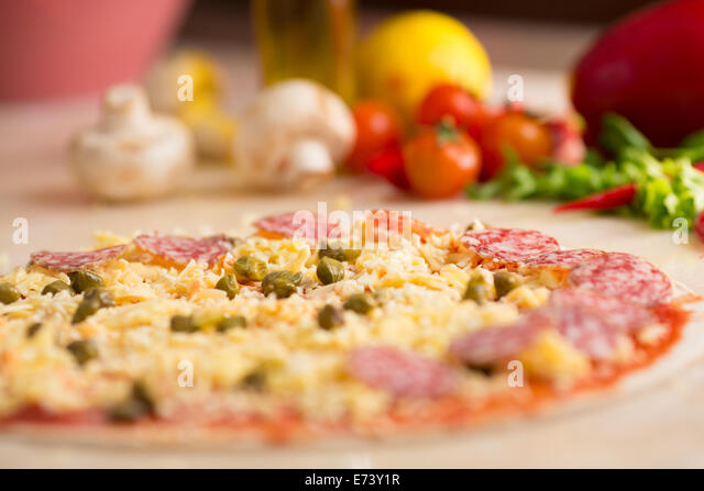 raw italian salami pizza on table with ingredients - Stock Image