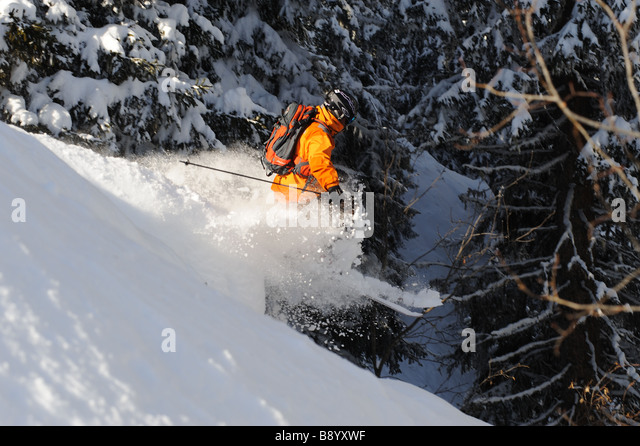 Skier jumps over a bump in deep powder - Stock Image