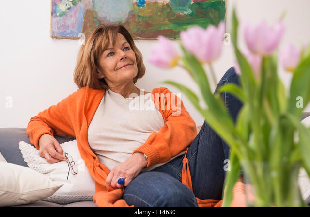 Senior woman day dreaming while sitting on sofa, Munich, Bavaria, Germany - Stock-Bilder