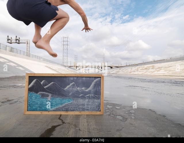 Man pretending to jump into lake, Los Angeles River, Los Angeles, California, USA - Stock Image