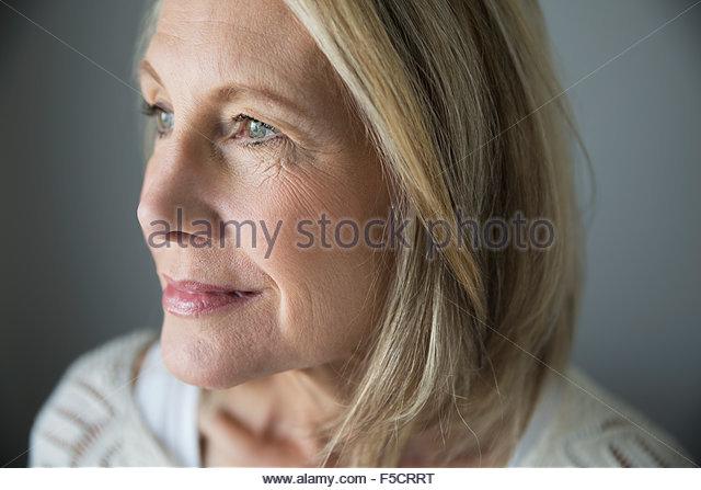 Close up portrait pensive senior woman looking away - Stock Image
