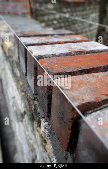 Building of a garden wall with Cotswold stone and reclaimed red bricks UK - Stock-Bilder