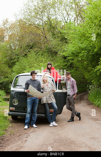 Friends by camper van with map - Stock Image