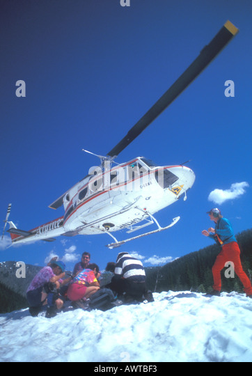 Helicopter Landing on Snow to Pick Up Hikers Canada - Stock Image