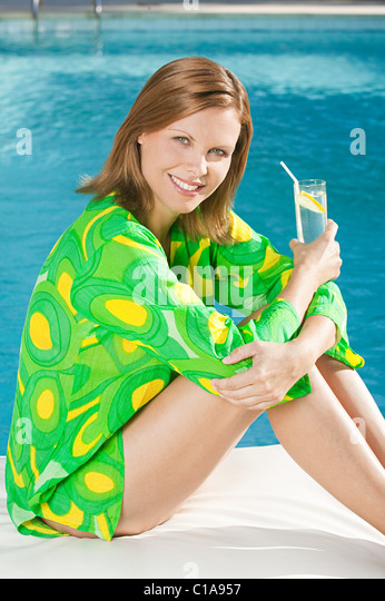 Young woman at poolside with soft drink - Stock Image