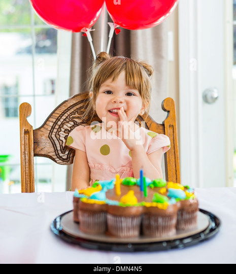 Happy Girl Sitting In Front Of Birthday Cake - Stock Image