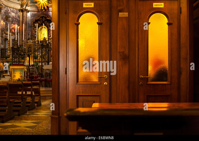 Priest hearing confession in confessional box booth in Roman Catholic Church Sanctuary of the Madonna di San Luca - Stock-Bilder