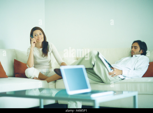 Young couple sitting on couch, man reading while woman uses cell phone - Stock Image