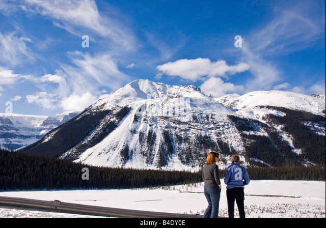 Two women alone in the Columbia Icefield Canada on a perfect winter day with snow blue sky perfect weather condition - Stock Image