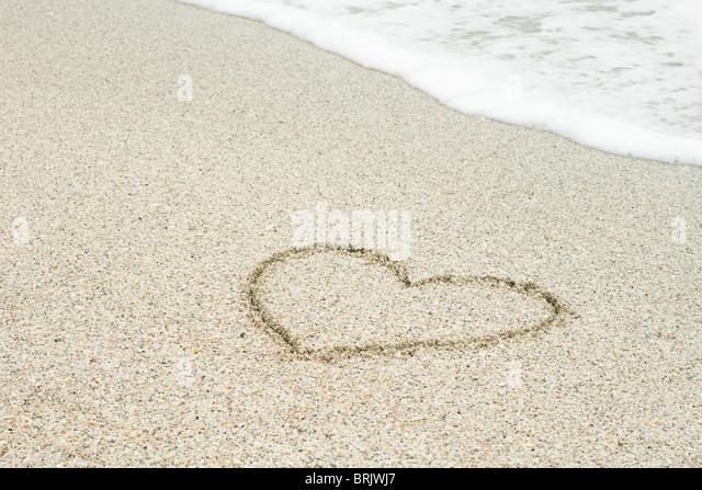 Heart drawn in sand at the beach - Stock-Bilder