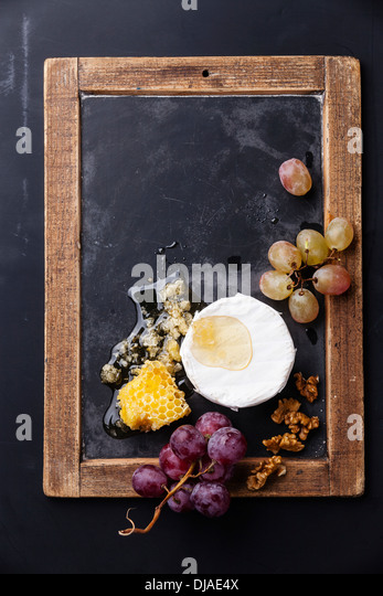 Cheese with honey, nuts and grapes on vintage slate chalk board - Stock Image