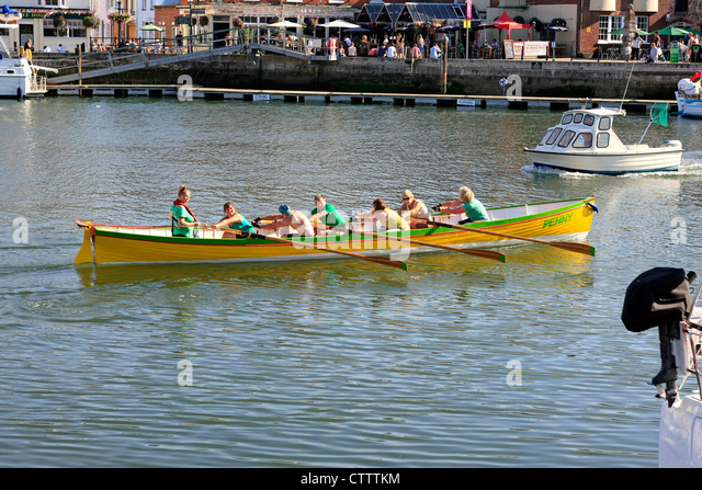 Middle aged people rowing a Cornish Gig boat named Penny through Weymouth Harbour - Stock Image