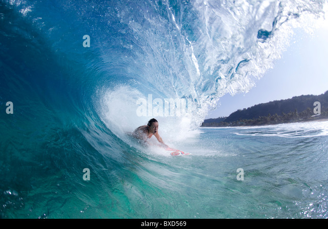 A water view of a surfer girl in the tube, in Hawaii. - Stock Image
