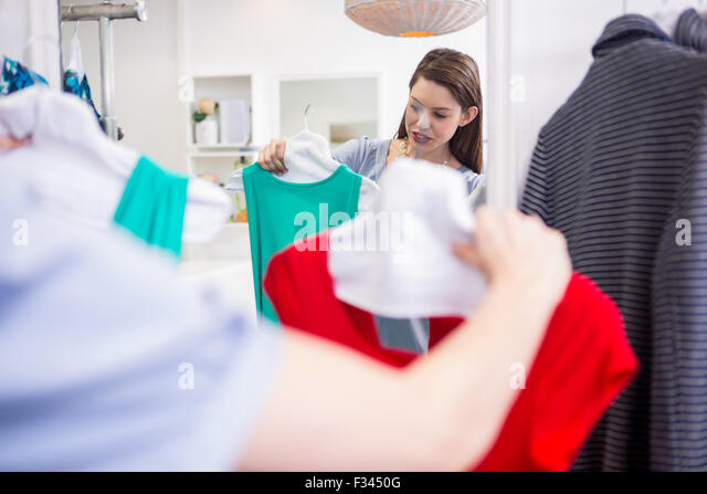 Woman deciding between two dresses - Stock Image