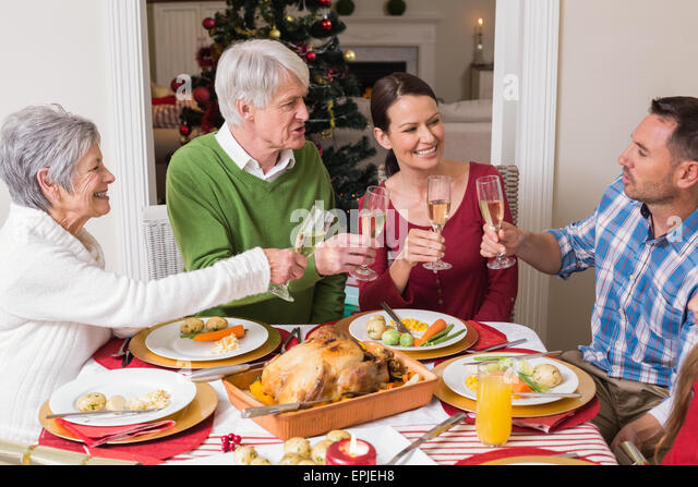 Portrait of happy family toasting at christmas dinner - Stock Image