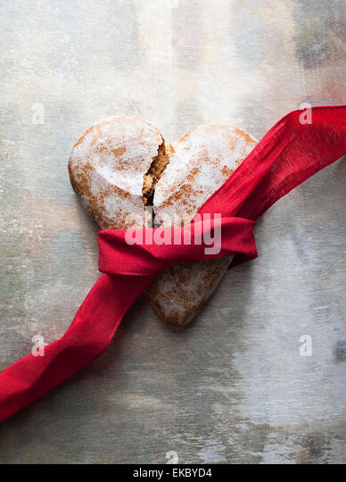 Broken heart-shaped gingerbread cookie with red ribbon - Stock Image