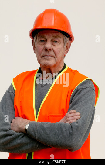Man (60) wearing orange high-visibility safety vest and hard-hat, looking at camera, plain background - Stock Image