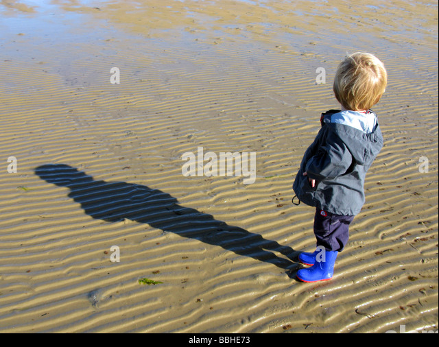 Boy alone on beach looking backwards - Stock Image