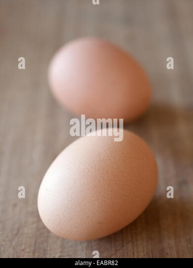 Two brown eggs on a wood surface. - Stock Image