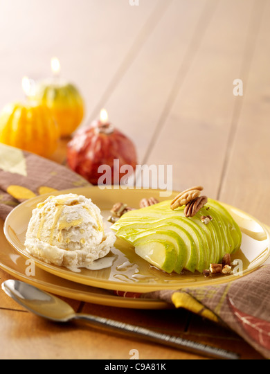 Sliced pears with pear ice cream topped with walnuts - Stock Image