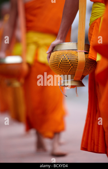the procession of monks at dawn through the town to collect gifts of food, Luang Prabang, Laos - Stock-Bilder