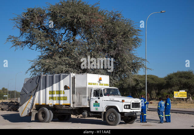 A waste-disposal truck with municipal workers on the outskirts of Maun, Botswana - Stock Image