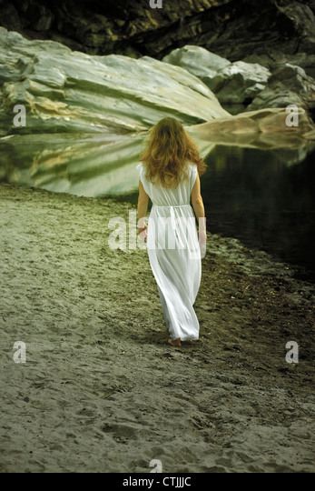 a woman in a white dress walks barefoot along the beach - Stock Image
