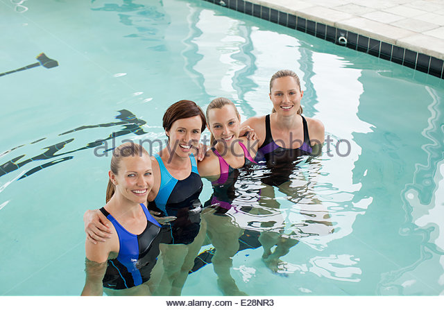 Portrait of smiling women in a row in swimming pool - Stock Image