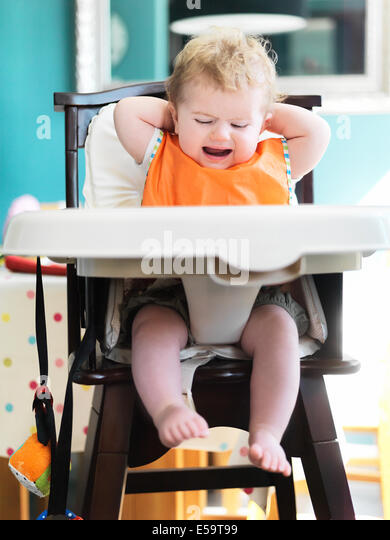 Baby girl crying in high chair - Stock Image