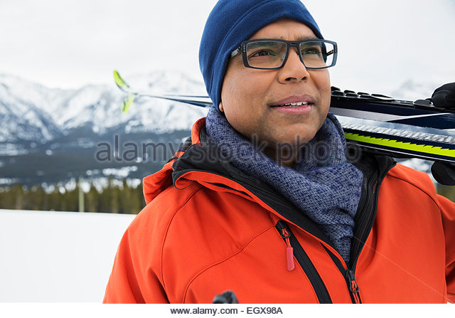 Man with skis in snowy field - Stock Image