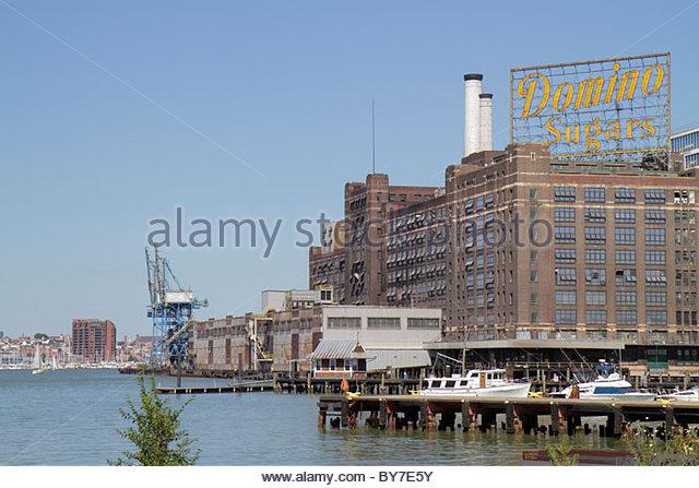Maryland Baltimore Patapsco River port waterfront Domino Sugar sugarcane refining plant sign smokestack dock business - Stock Image