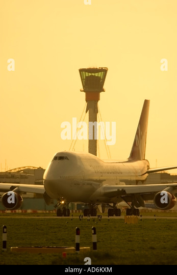 Commercial airliner and new air traffic control tower at London Heathrow Airport England UK - Stock Image