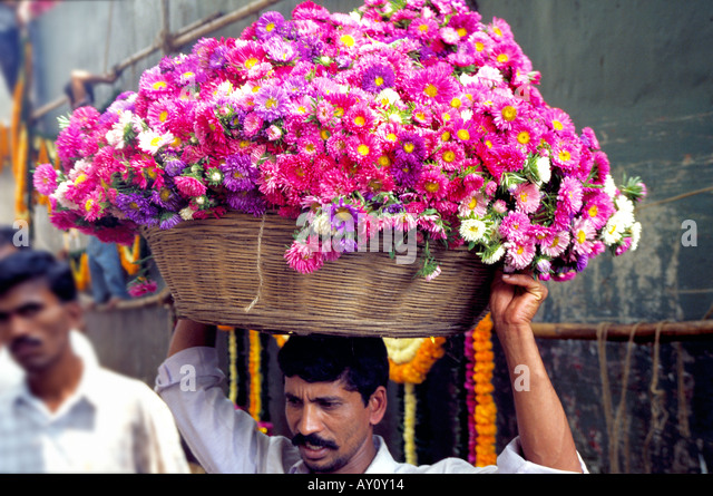 A porter carrying a cane basket with a fragrant load at Dadar Flower Market the biggest wholesale flower market - Stock-Bilder