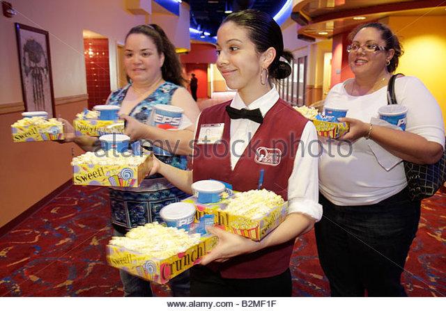 Indiana Portage Portage 16 IMAX movie theater complex Hispanic woman women teen girl popcorn attendant job uniform - Stock Image