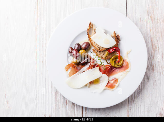 Appetizer with ham, cheese and olives on white plate - Stock Image