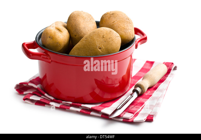 the uncooked potatoes and old wooden peeler - Stock Image