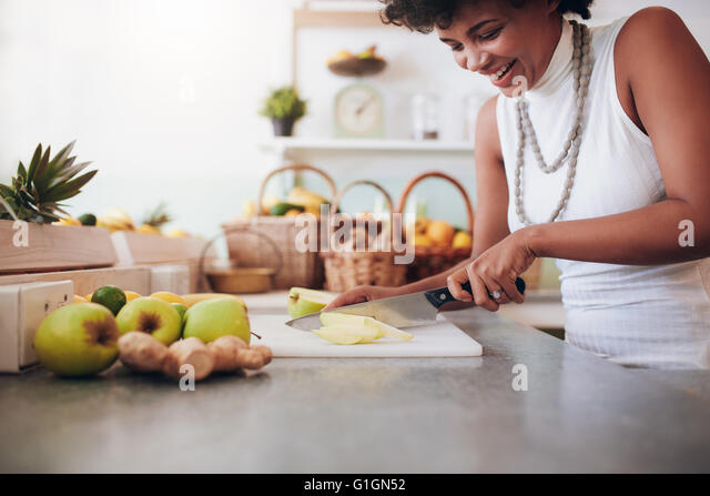 Attractive young woman chopping up fresh fruit for smoothie. Female working at juice bar. - Stock Image
