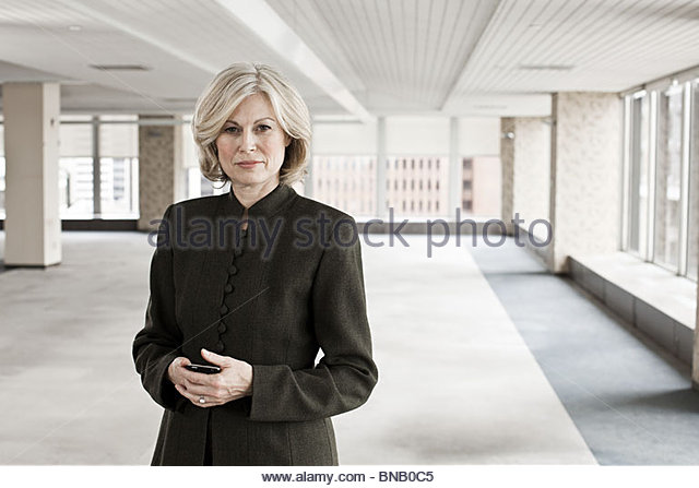 Businesswoman in empty office space - Stock Image