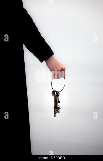 a man in a black coat holding a keyring with old keys - Stock Image