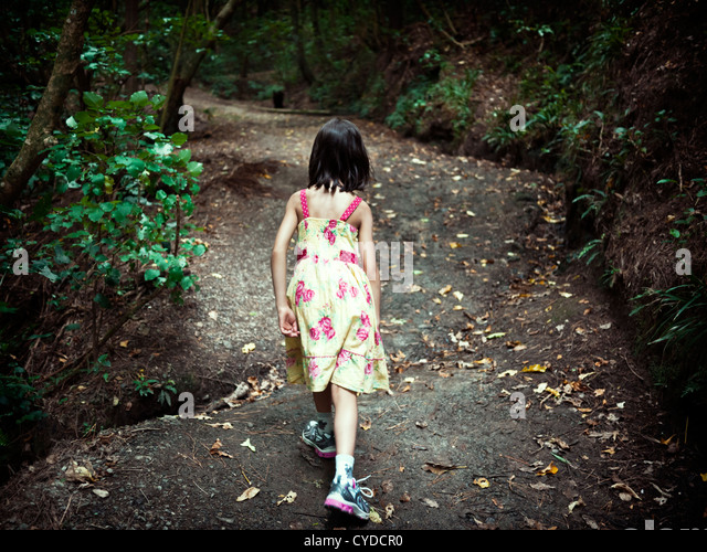 Girl strides up hill on woodland path. - Stock Image