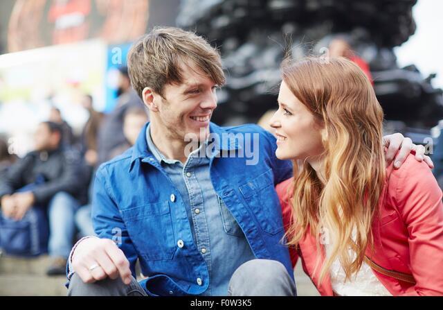 Tourist couple sitting at Piccadilly Circus, London, UK - Stock-Bilder