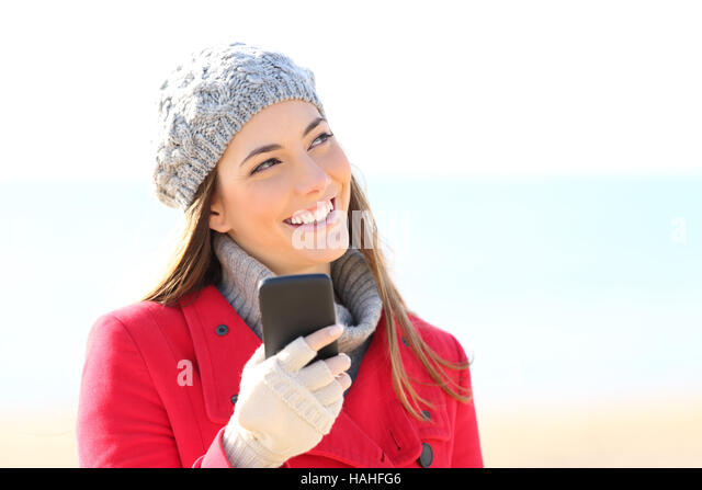 Front view portrait of a happy girl wearing coat thinking and looking sideways with a phone on the beach in winter - Stock Image