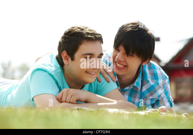Happy gay lovers lying on the lawn - Stock Image