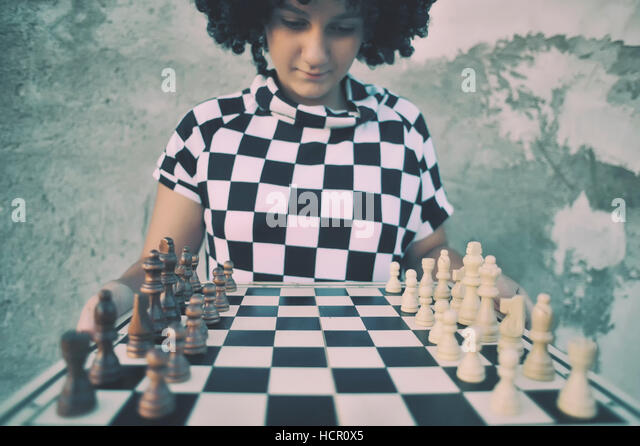 Girl playing a game of chess. - Stock Image