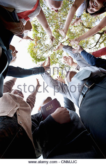 Low angle view of people cheering in circle - Stock Image