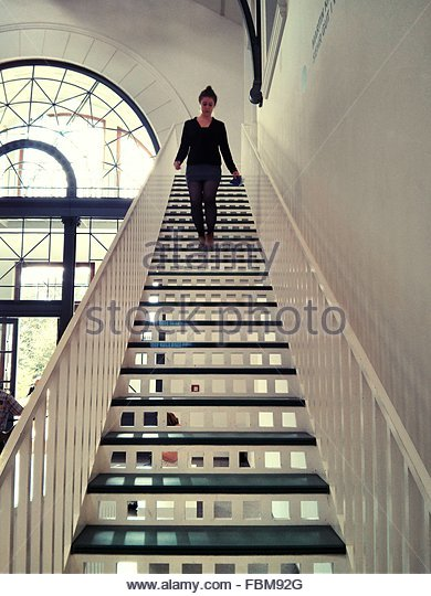 Young Woman Moving Down Steps At Home - Stock-Bilder