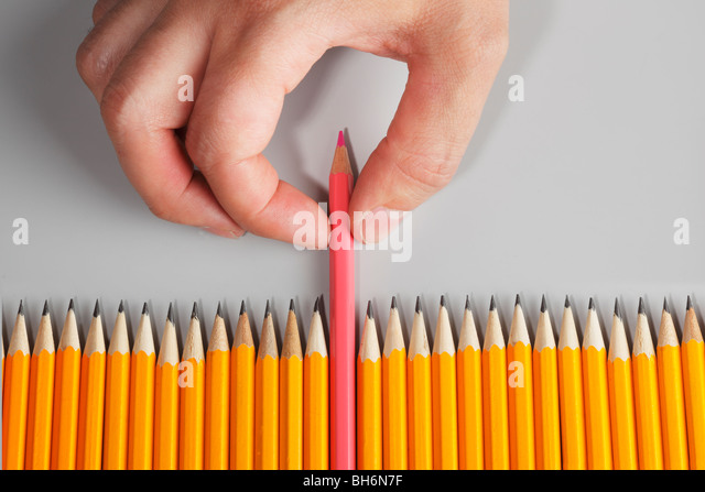 Hand choosing a pink pencil - Stock Image