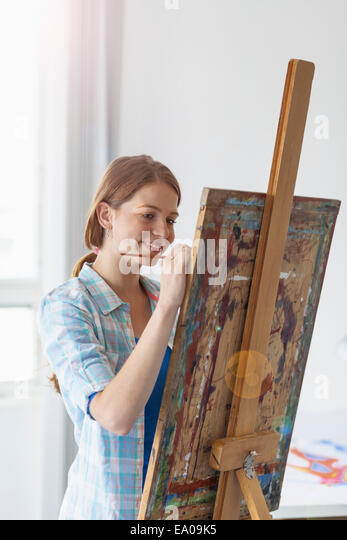 Female artist painting at easel - Stock Image